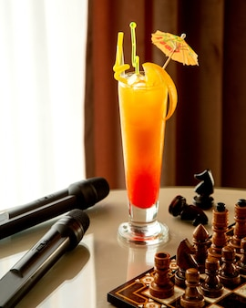 A glass of orange cocktail garnished with cocktail umbrella ad straws