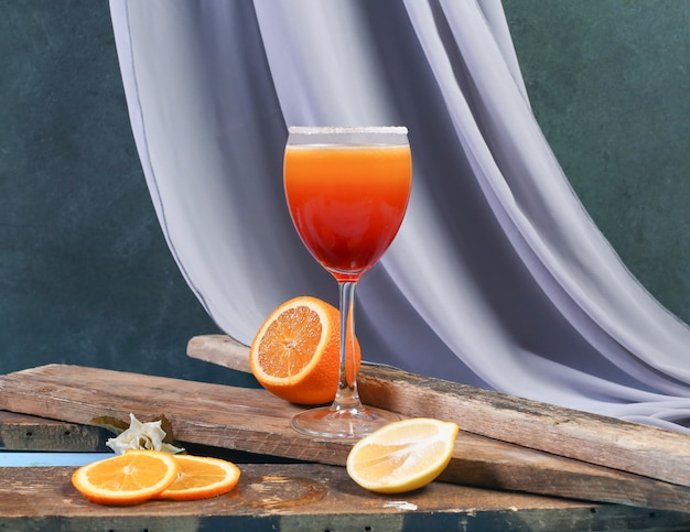 A glass of orange cocktail on a piece of wood.