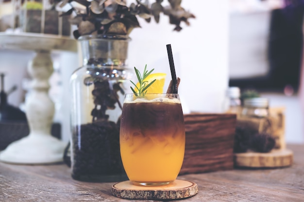 A glass of orange cold brew iced coffee