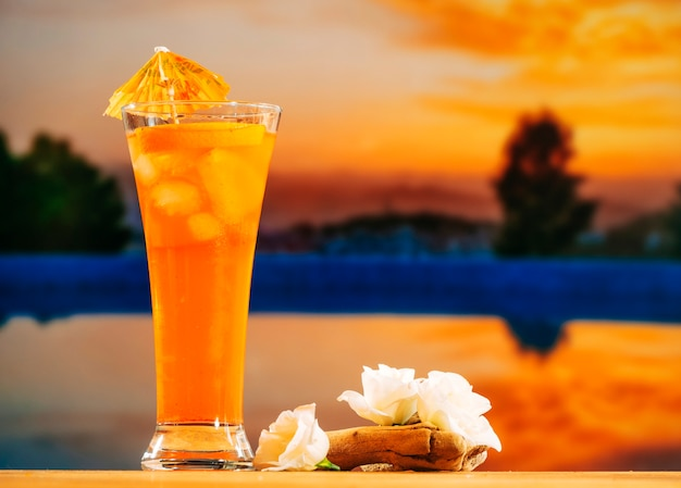 Glass of orange drink and white flowers
