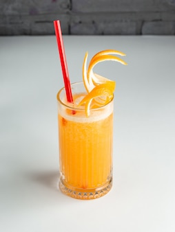 A glass of orange juice garnished with orange zest