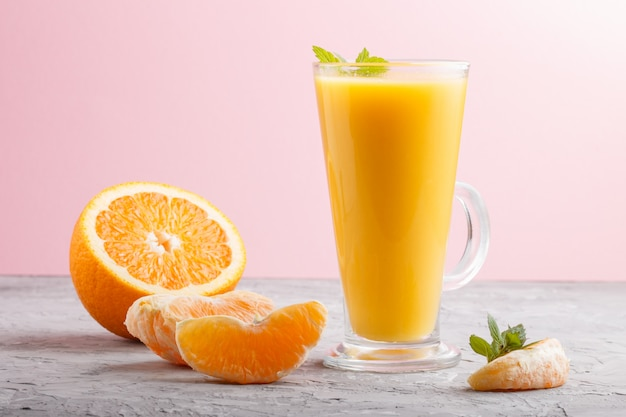 Glass of orange juice on a gray and pink background. side view