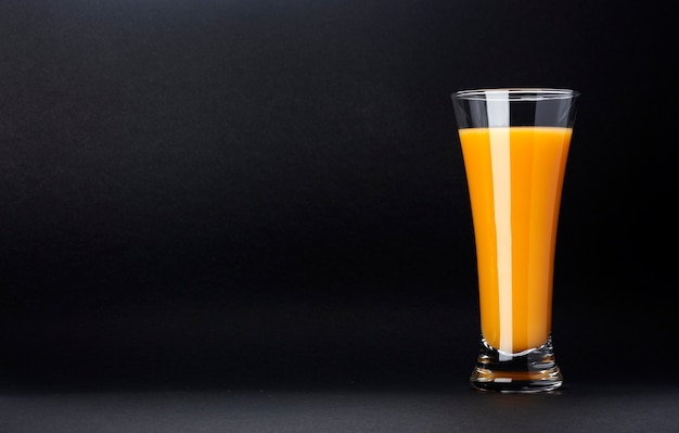 Glass of orange juice isolated on black with copy space for text, fresh citrus cocktail