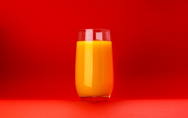Glass of orange juice isolated on red background