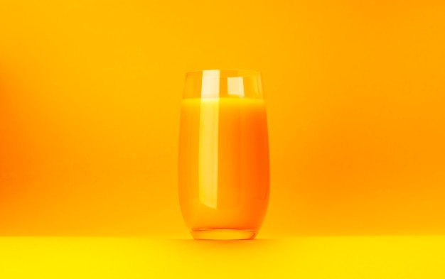 Glass of orange juice isolated on yellow background with copy space