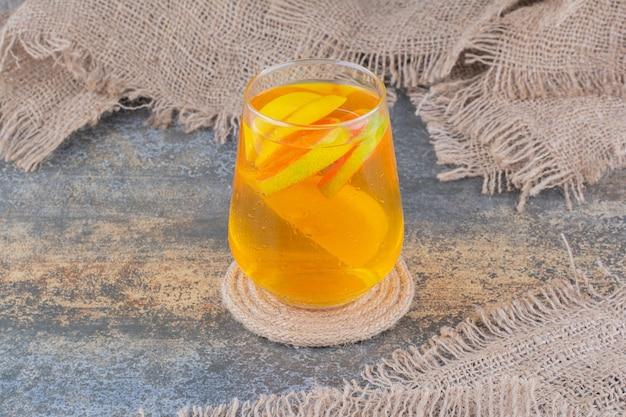 Un bicchiere di succo d'arancia su sfondo marmo. foto di alta qualità