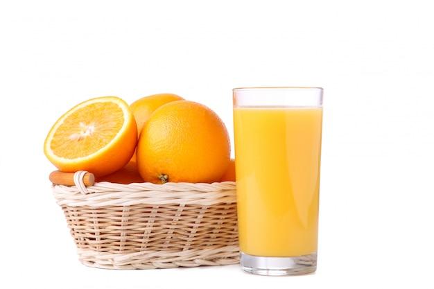 Glass of orange juice and orange in basket