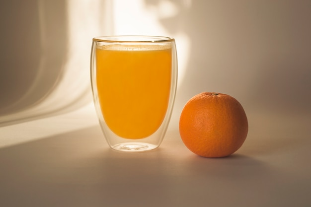 Glass of orange juice and orange on a light background in the shade