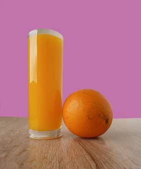 Glass of orange juice and oranges on wooden floor