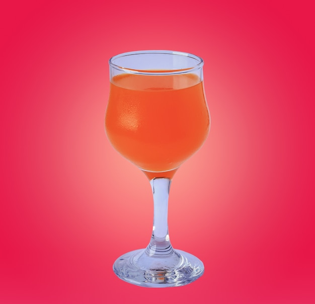 Glass of orange juice on pink background
