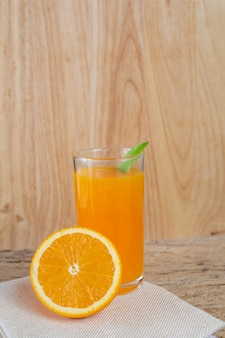 Glass of orange juice placed on wood.