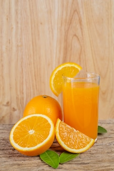 Glass of orange juice placed on wood.