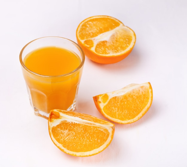 Glass of orange juice and slices of orange fruit on white background