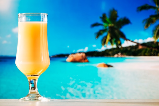 Glass of orange juice in tropical summer