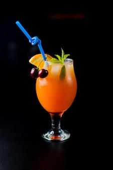 A glass of orange juice with cherries and mint in black background.