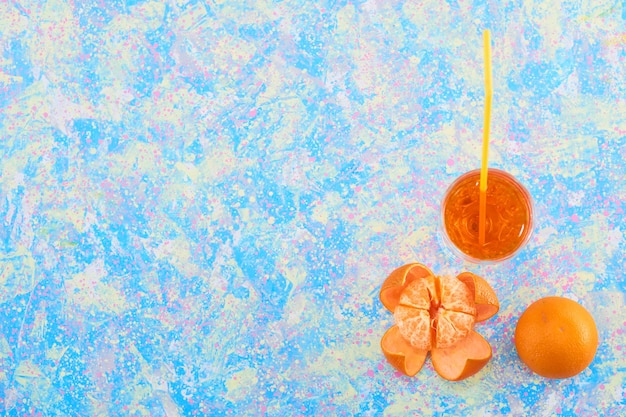 A glass of orange juice with mandarines around on blue background, top view. high quality photo