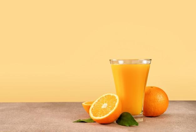 Glass of orange juice with oranges on light yellow background