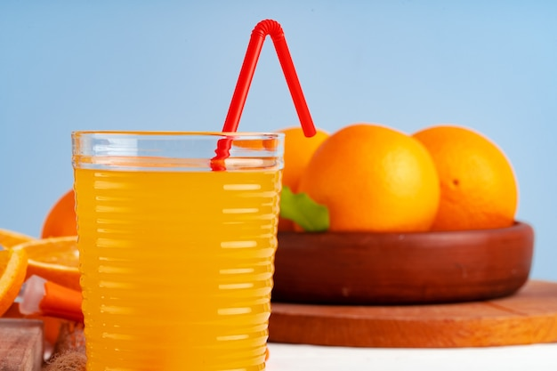 Glass of orange juice with red straw on table