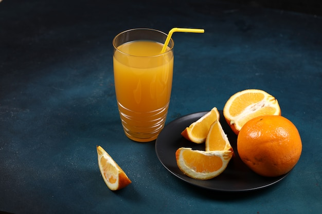 A glass of orange juice with sliced fruits in the black plate.