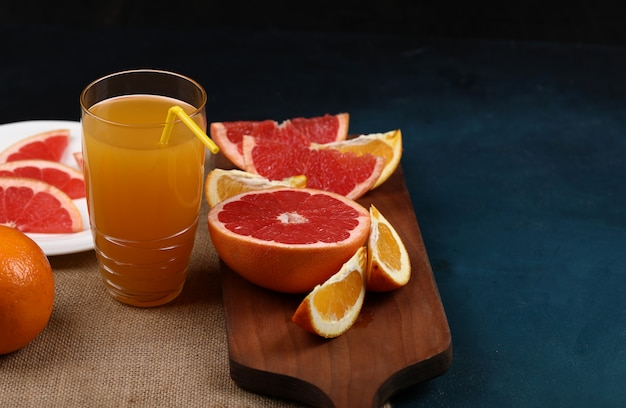 A glass of orange juice with sliced fruits.