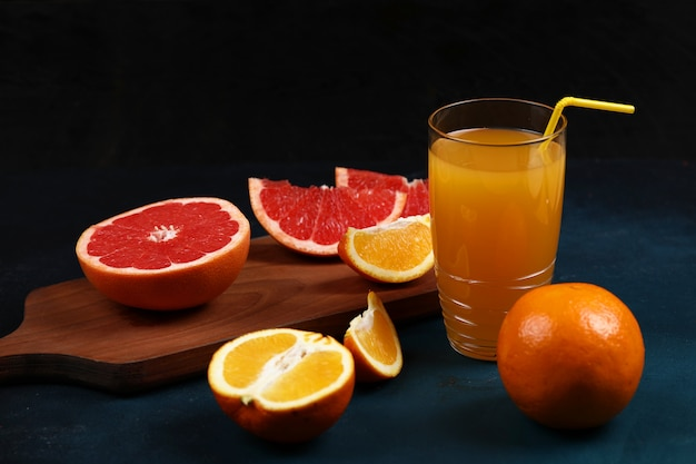 A glass of orange juice with sliced orange and grapefruit.