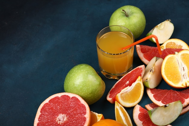 A glass of orange juice with sliced tropical fruits.