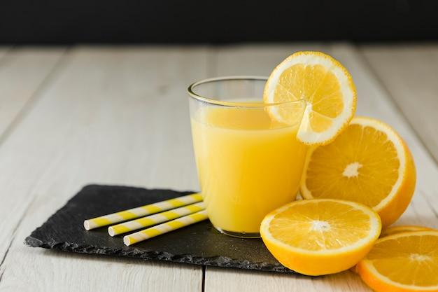 Bicchiere di succo d'arancia con cannucce