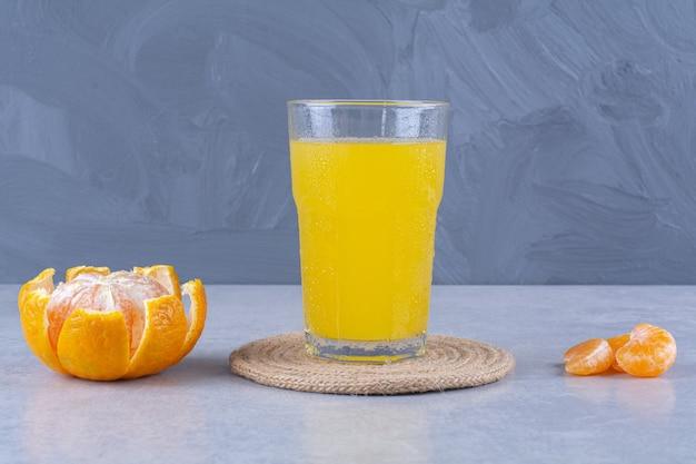 Un bicchiere di succo d'arancia su un sottopentola accanto al mandarino affettato sul tavolo di marmo.