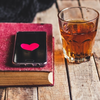 Glass of orange punch, book, smartphone and heart