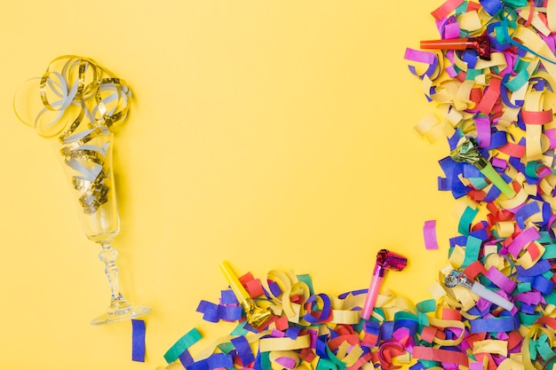 Glass and party horns near confetti