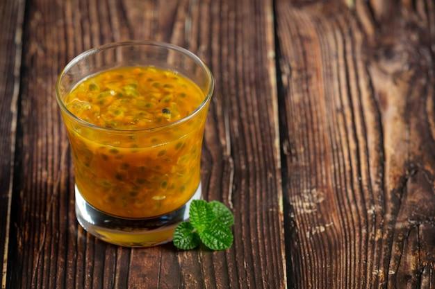 Un bicchiere di succo di frutto della passione posto sul pavimento di legno