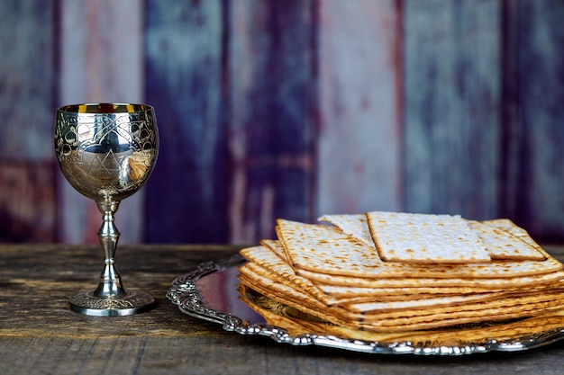 Glass of passover wine and matzah closeup. backlit blurred matzah texture in background.