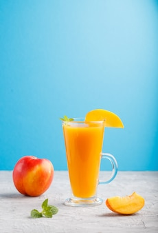 Glass of peach juice on a gray and blue background, side view