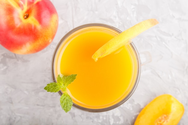 Glass of peach juice on a gray concrete background