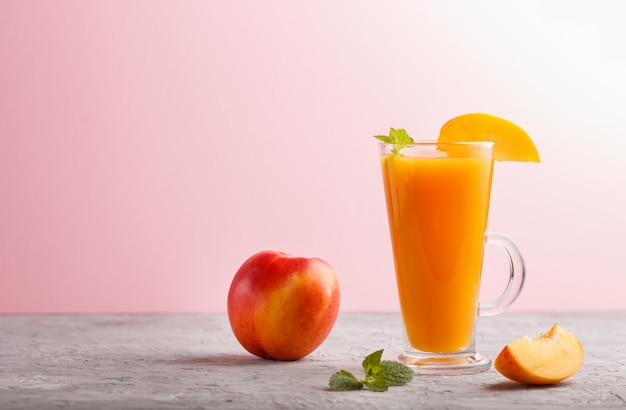 Glass of peach juice on a gray and pink background. side view