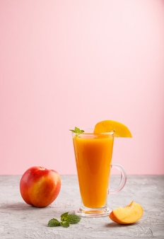 Glass of peach juice. side view