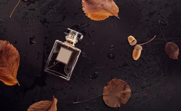 青銅の乾燥した葉の上のガラス香水瓶