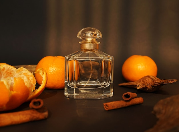 Glass perfume bottle with citrus and cinnamon sticks on wooden table