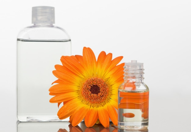 A glass phial and an orange gerbera with a glass flask