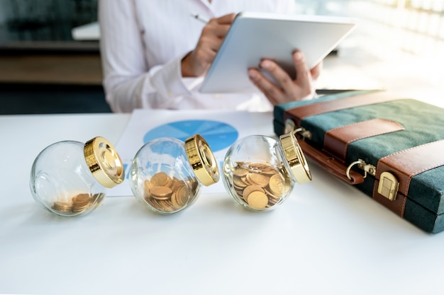 Glass piggy bank on the white table with business women note on the tablet