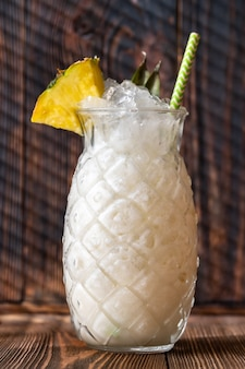 Glass of pina colada cocktail garnished with pineapple wedge