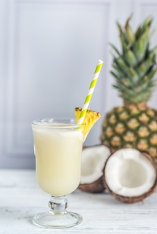 Glass of pina colada garnished with pineapple wedge