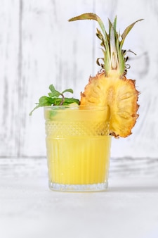 Glass of pineapple tiki style cocktail on white background