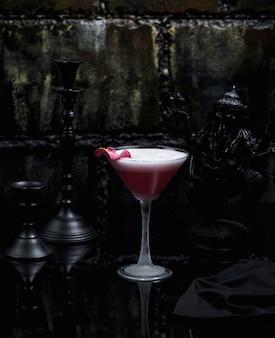 A glass of pink cosmopolitan in dark background
