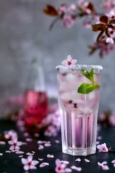 Glass of pink rose champagne, cider or lemonade with ice and mint and cherry blossoms