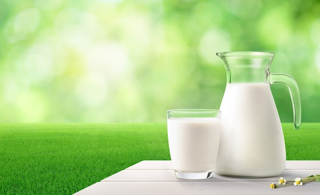 Glass and pitcher of fresh milk on white wooden table with green blurred background.