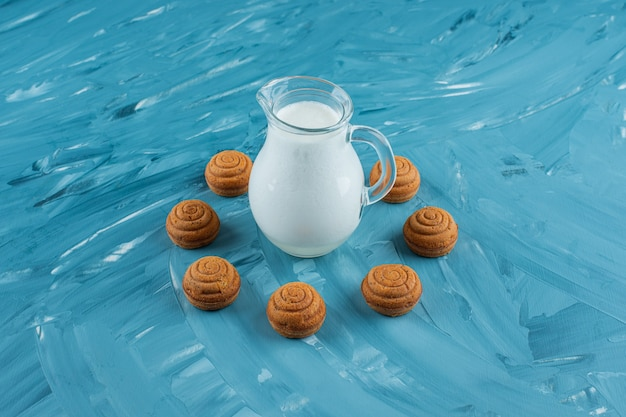 A glass pitcher of fresh milk with sweet round cookies on a blue surface