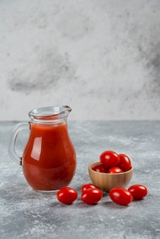 A glass pitcher full of tomato juice with a wooden bowl of cherry tomato.