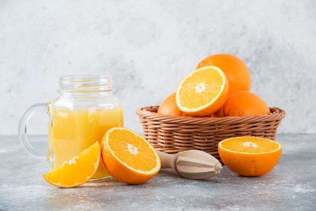 A glass pitcher of juice with fresh orange fruits on stone table .