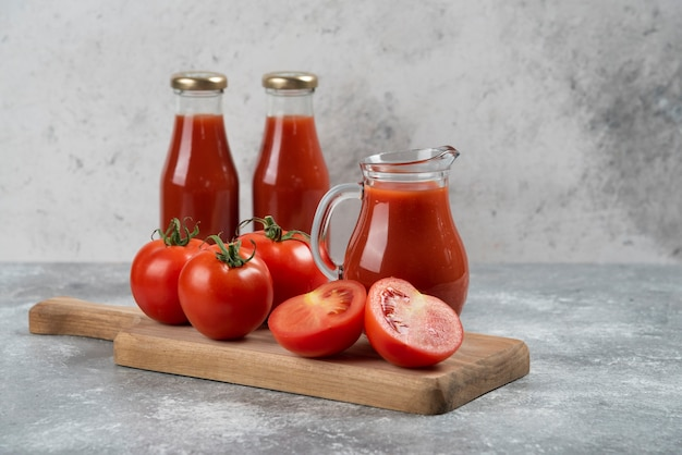 A glass pitcher of juice with fresh tomatoes.